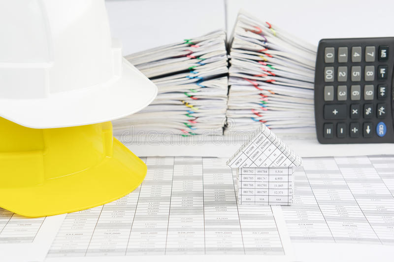 House and white on yellow engineer hat on finance account. Have blur pile overload document of report and receipt with colorful paperclip with calculator place royalty free stock photography