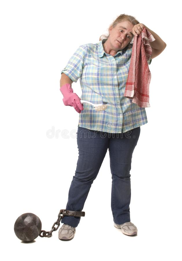 Overworked Woman in Chains. A house wife with a ball and chain, concept of being over burdened stock image