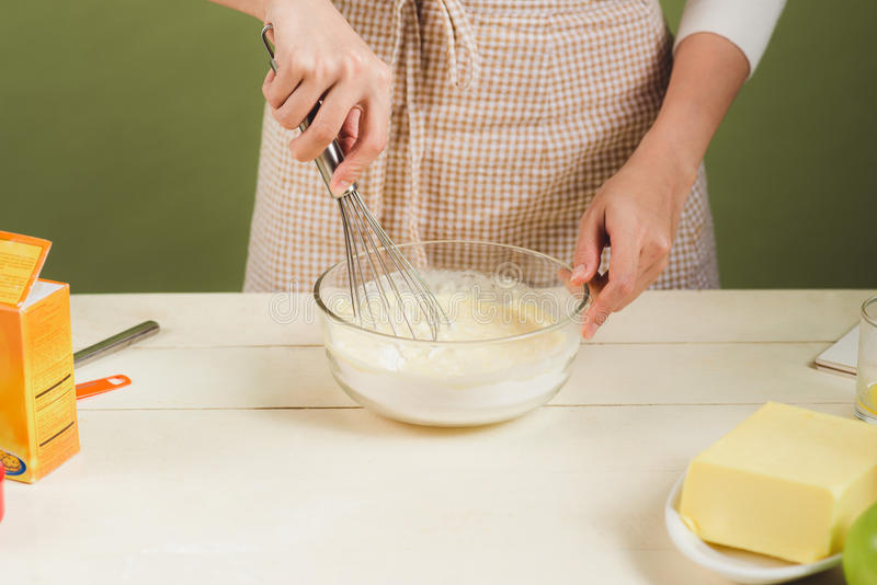 House wife wearing apron making. Steps of making cooking chocolate cake. Preparing dough, mixing ingredients royalty free stock photography