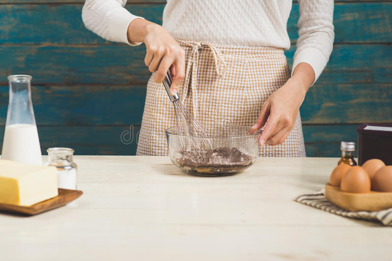 House wife wearing apron making. Steps of making cooking chocolate cake. Preparing dough, mixing ingredients royalty free stock photo