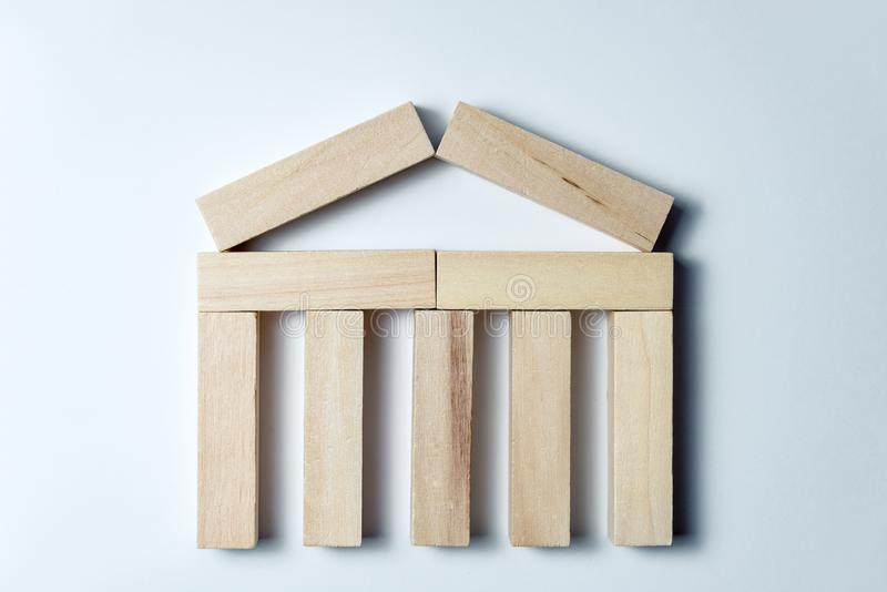 A house of wooden cubes, as a symbol of resilience, strength of business and strategy, on an uneven white background. Horizontal. A house of wooden cubes, as a stock photos