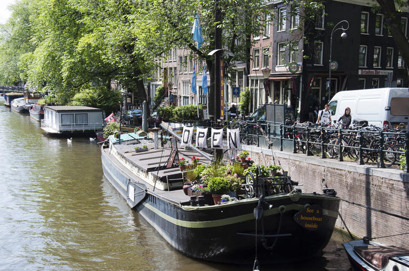 Houseboat museum on canal. AMSTERDAM - JUNE 10: Living boat on June 10, 2011 in Amsterdam. There are around 2,500 houseboats along 165 canals where locals live stock image