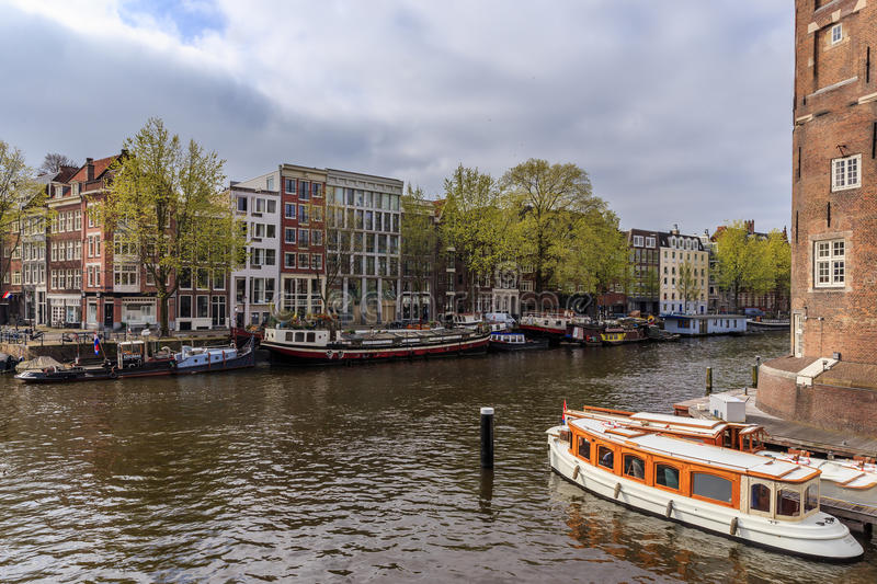 Houseboat and ship on the canal in Amsterdam royalty free stock photography