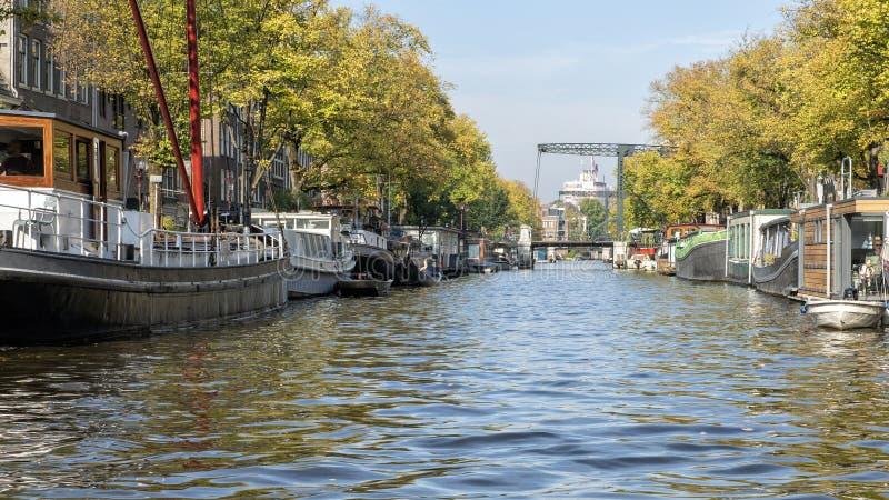 Houseboats που ευθυγραμμίζουν ένα κανάλι στο Άμστερνταμ, οι Κάτω Χώρες στοκ φωτογραφία