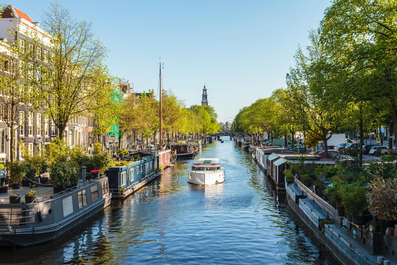 Houseboats on the Dutch Prinsengracht canal in Amsterdam. Summer view of houseboats on the Dutch Prinsengracht canal in Amsterdam royalty free stock photography