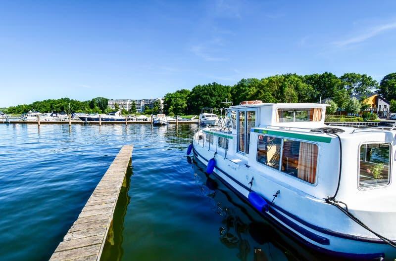 Houseboats i jachty cumują w Goehren-Lebbin Niemcy przy jetty jeziorny Fleesensee zdjęcie stock