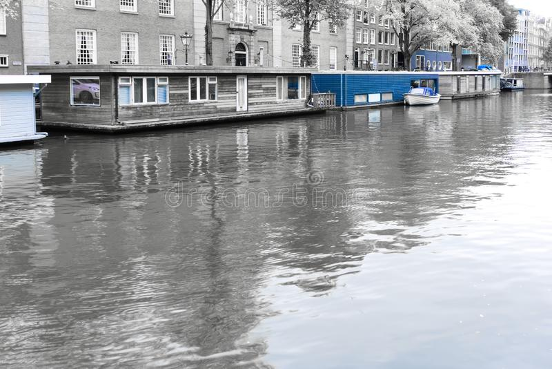 Houseboats in the nieuwe prinsengracht amsterdam. In black and white with blue saturated to stay in blue royalty free stock photos