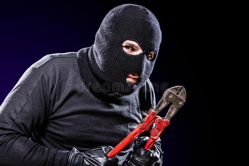 Housebreaker Portrait. A burglar wearing a balaclava holding huge wire cutters over black background stock images
