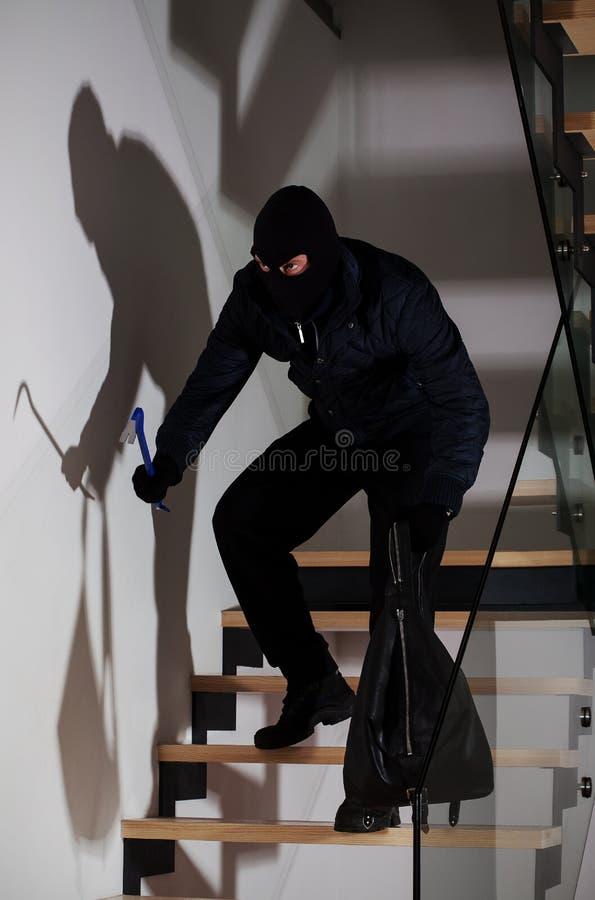 Burglar creeping on stairs. Burglar with a crowbar and bag creeping on stairs stock photography