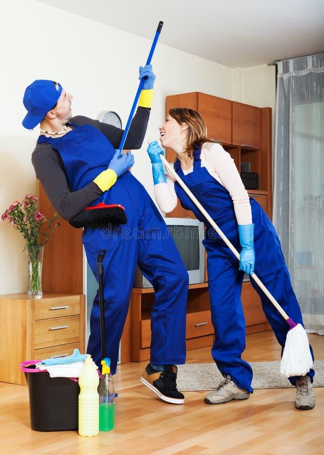 Housecleaners schoonmakend huis stock foto