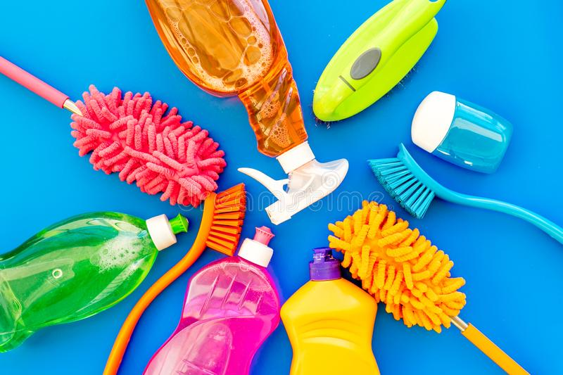 Housecleaning with detergents, soap, cleaners and brush in plastic bottles on blue background top view mockup royalty free stock images