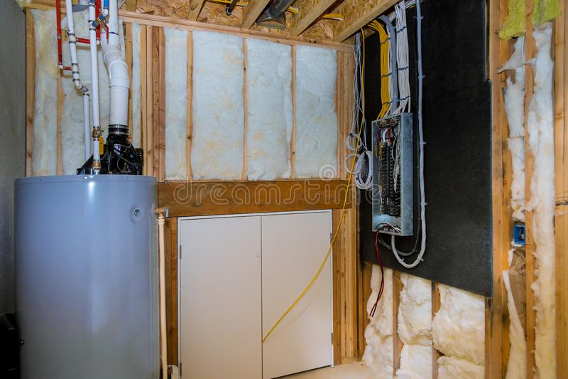Household boiler house with heat wired electrical terminals on metal bar wall insulation in wooden house, building under stock photography