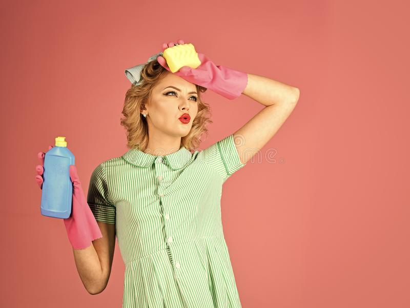 Household chores. Housekeeper in uniform with clean spray, sponge. Retro woman cleaner on pink background. Cleanup, cleaning services, wife, gender. Cleaning stock photos