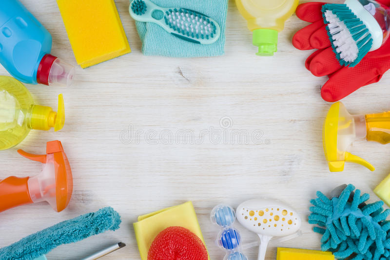 Household cleaning products on wooden background with copyspace in middle royalty free stock photos