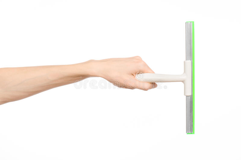 Household cleaning and washing windows theme: man's hand holding a green scraper windows isolated on a white background in the stu. Household cleaning and royalty free stock photos