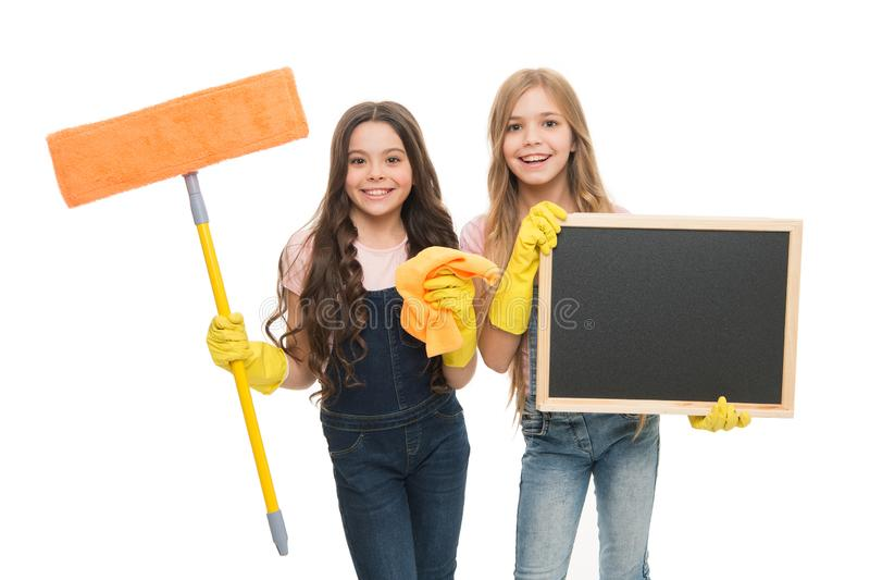Household duties. Girls with rubber protective gloves ready for cleaning. Little helper. Girls cute kids cleaning. According to duty, blackboard copy space stock image