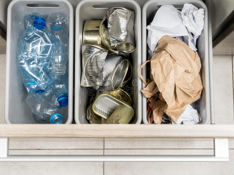 Household garbage segregation. Three plastic trash bins in kitchen cabinet with segregated household garbage - PET bottles, paper and metal cans shot from above stock images
