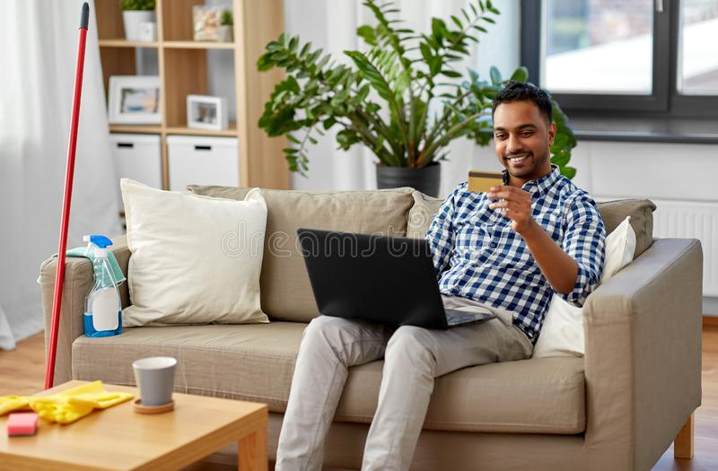 Man with laptop shopping online after cleaning. Household, housework and technology concept - indian man with laptop computer and credit card shopping online royalty free stock photo