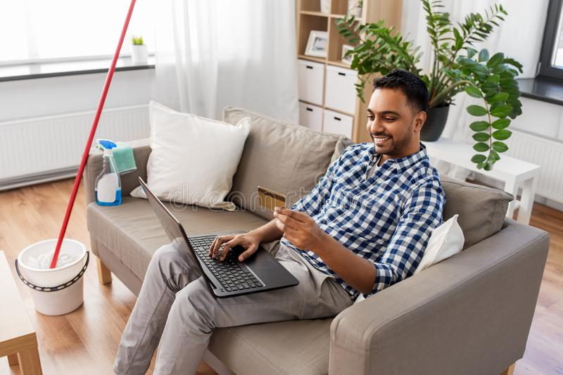 Man with laptop shopping online after cleaning. Household, housework and technology concept - indian man with laptop computer and credit card shopping online stock images