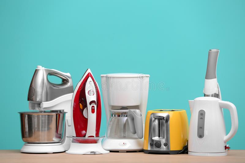 Different household and kitchen appliances on table against color background. Interior element royalty free stock photography