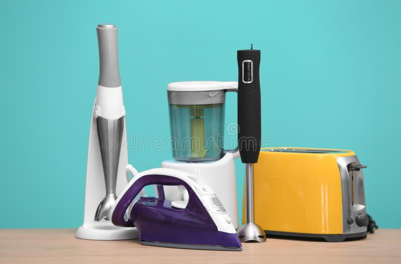 Household and kitchen appliances on table. Against color background. Interior element stock images