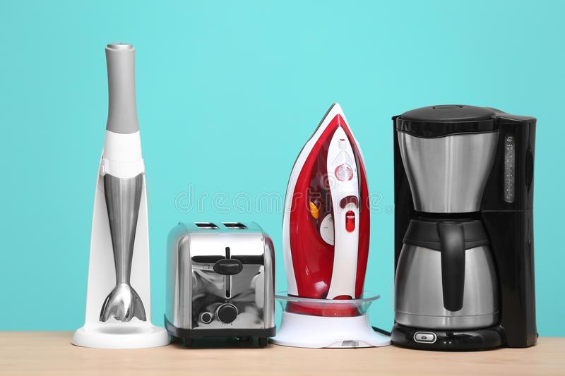 Household and kitchen appliances on table. Against color background. Interior element royalty free stock photography