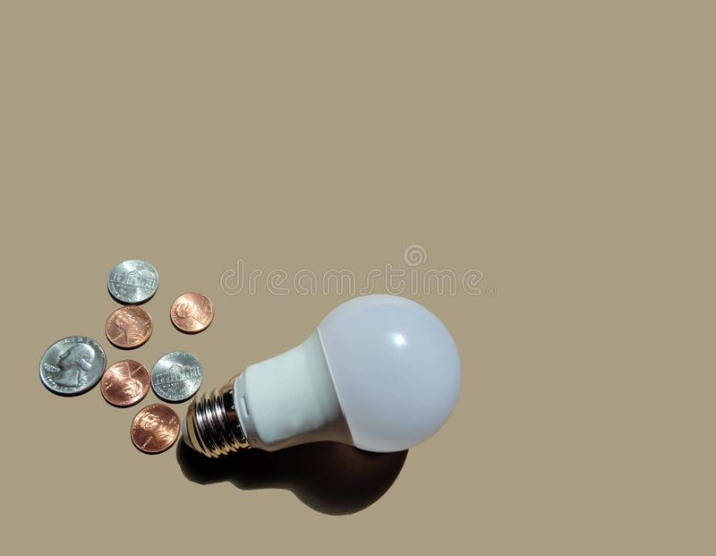 Household LED Energy Saving Light Bulb With Coins stock photo