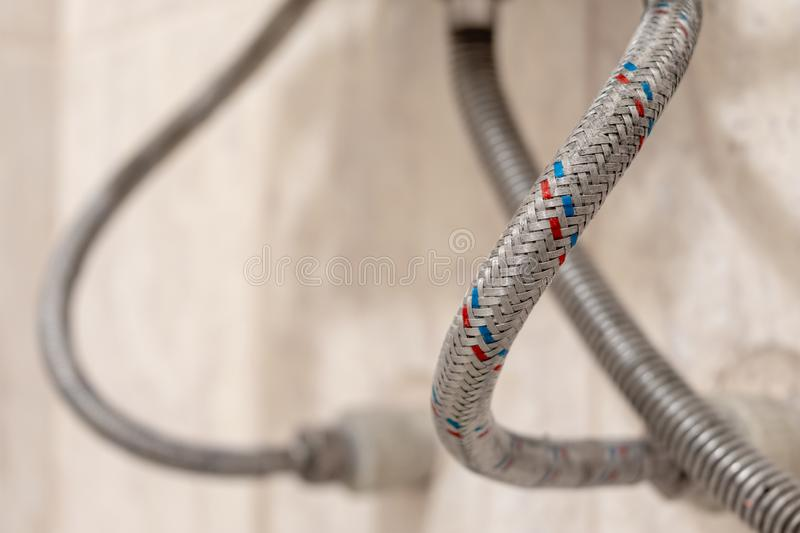 Household-reinforced hose for water supply. Selective focus. next to the gas hose royalty free stock images