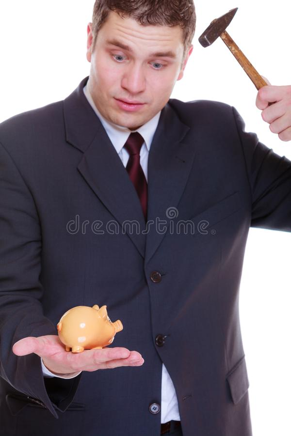 Man trying to break piggy bank with hammer. Household savings concept. Man wearing tuxedo trying to break piggy bank with hammer stock photo