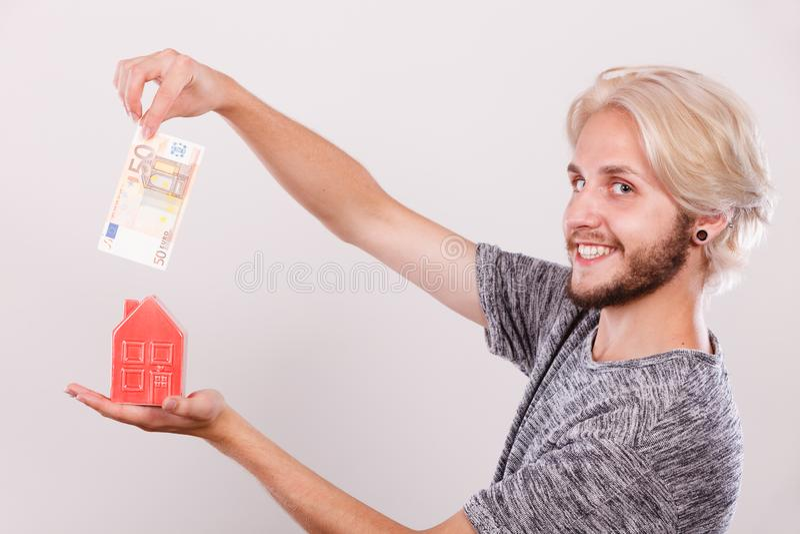 Man putting money into house piggybank royalty free stock photo