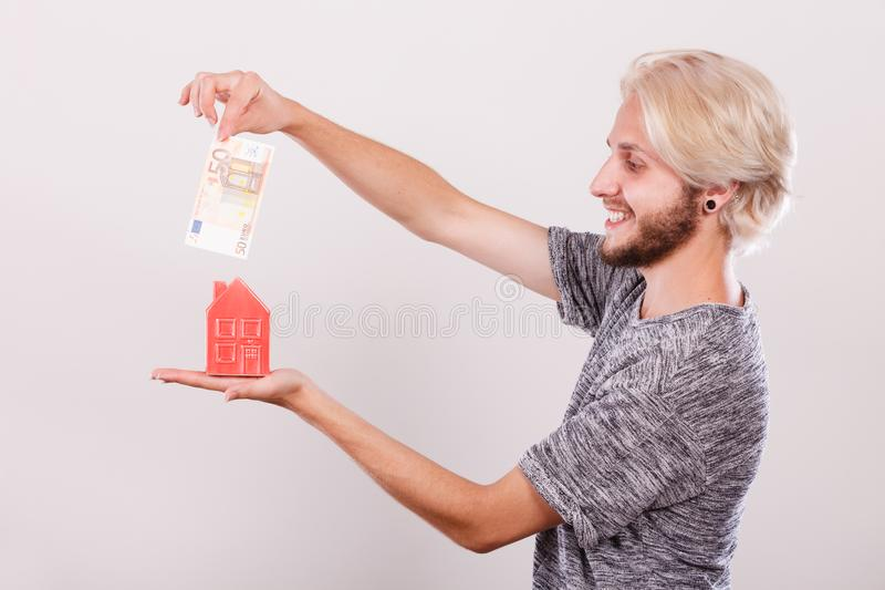 Man putting money into house piggybank royalty free stock photography