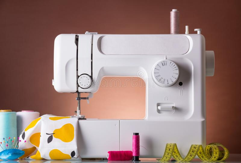 Household sewing machine, accessories, fabric under presser foot royalty free stock images