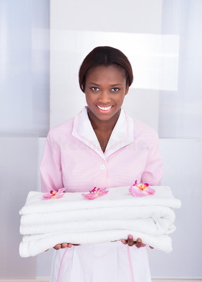 Housekeeper carrying towels in hotel. Smiling young female housekeeper carrying towels in hotel royalty free stock images