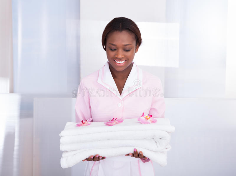 Housekeeper carrying towels in hotel. Smiling young female housekeeper carrying towels in hotel royalty free stock photo