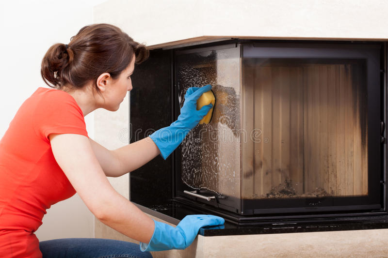 Housekeeper cleaning the fireplace. Horizontal view of housekeeper cleaning the fireplace royalty free stock photo