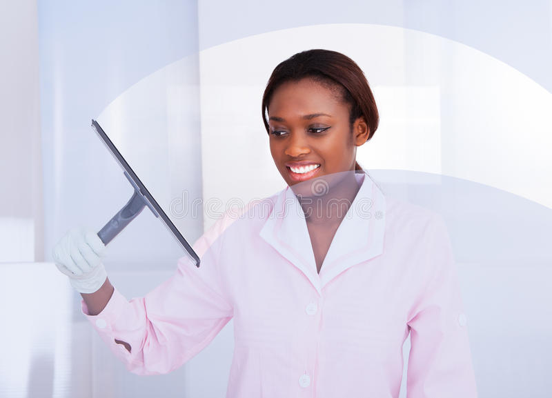 Housekeeper cleaning glass in hotel. Smiling African American housekeeper cleaning glass in hotel royalty free stock photo