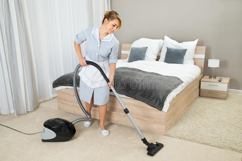 Housekeeper cleaning with vacuum cleaner. Female Housekeeper Cleaning Rug With Vacuum Cleaner In Hotel Room stock photos