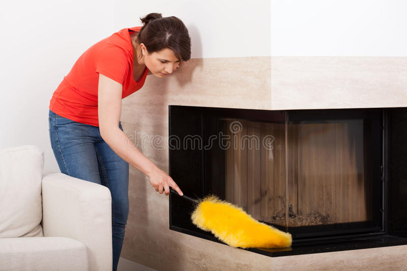 Housekeeper during dusting. Horizontal view of a housekeeper during dusting royalty free stock photography