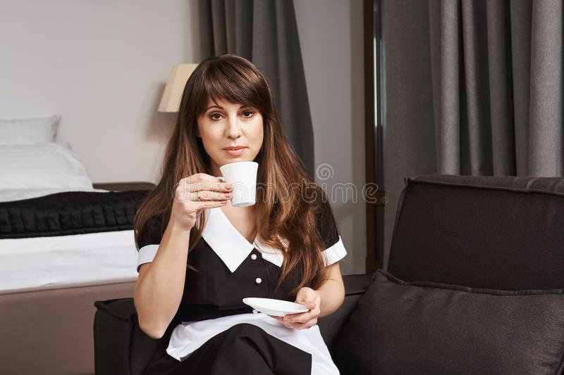 Housekeeper on guard of cleanness. Indoor shot of calm and confident maid in uniform sitting on sofa and holding cup royalty free stock images