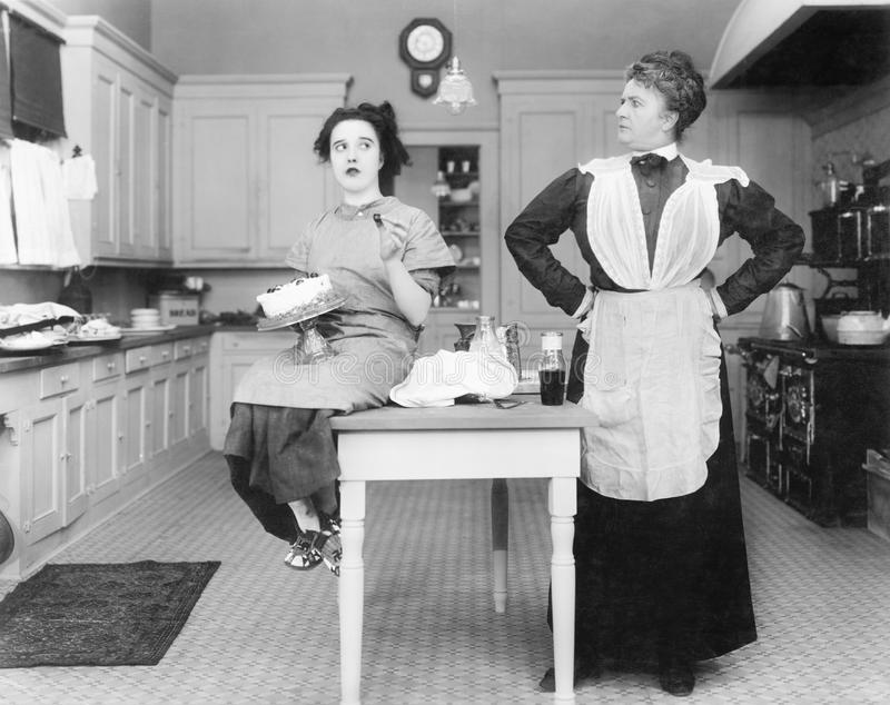 Housekeeper in the kitchen glaring at a young woman eating a cake. (All persons depicted are no longer living and no estate exists. Supplier grants that there royalty free stock image