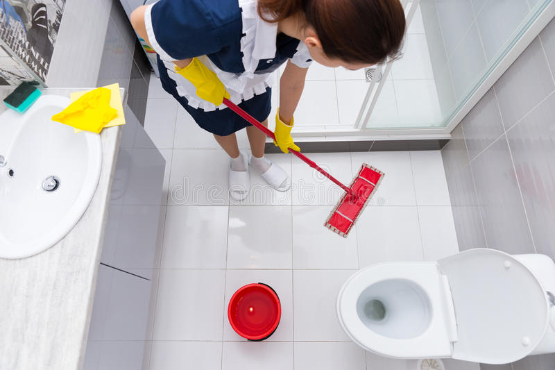 Housekeeper or maid mopping the floor royalty free stock photos