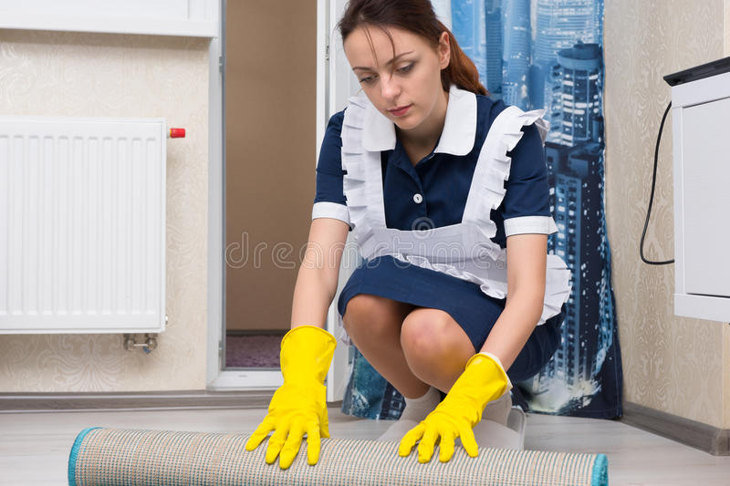 Housekeeper or maid rolling up a mat royalty free stock photo