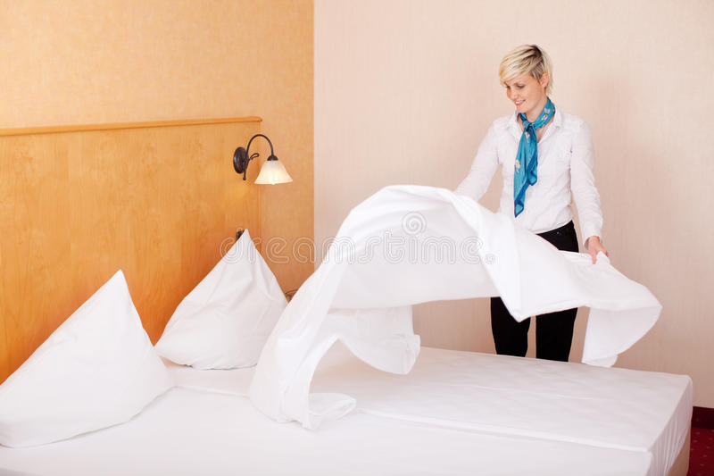 Housekeeper Making Bed In Hotel Room. Young female housekeeper making bed in hotel room royalty free stock image