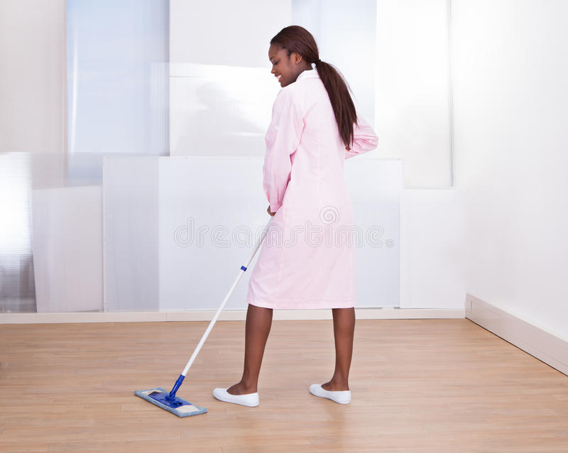 Housekeeper Mopping Floor In Hotel. Full length of female housekeeper mopping floor in hotel stock photo