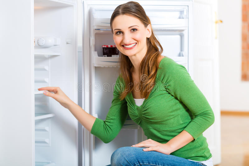 Housekeeper with Refrigerator. Young woman or housekeeper defrosts the refrigerator and wipes in clean stock photo