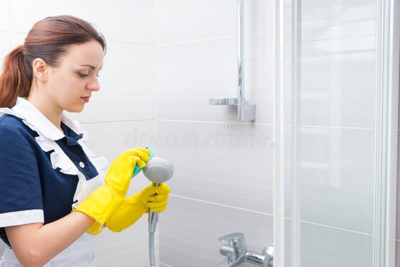 Housekeeper scrubbing down shower head stock photos