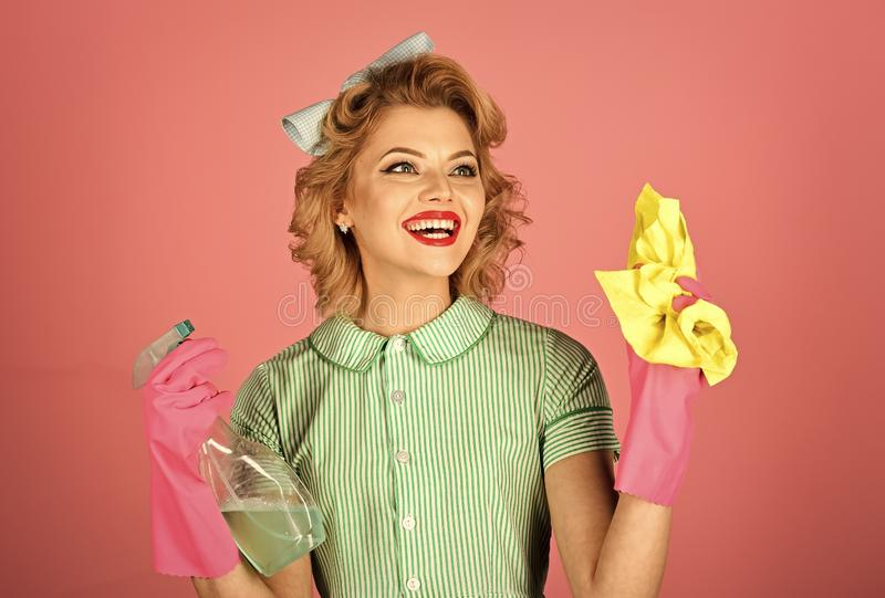 Housekeeper in uniform with clean spray, duster. Cleanup, cleaning services, wife, gender. Cleaning, retro style, purity. Pinup woman hold soup bottle, duster royalty free stock photography