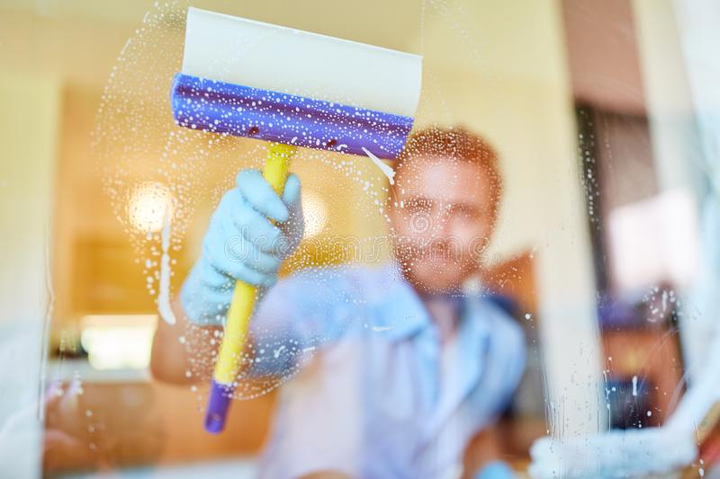 Housekeeper or window cleaner cleaning the window. Housekeeper or window cleaner at the window cleaning at home at the spring cleaning stock photo