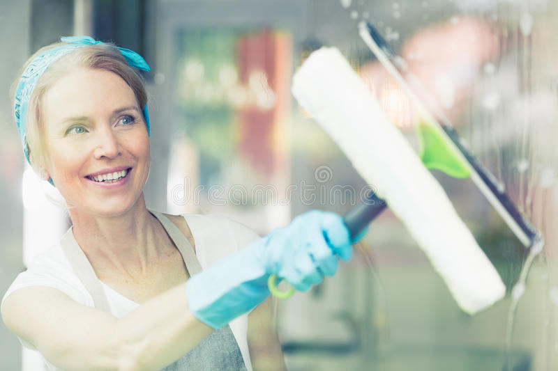 Housekeeper wipes window. Housekeeper wipes the water of the windows while holding in hand wiper royalty free stock images