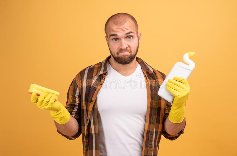 Housekeeping and cleaning concept. Unhappy confused young male janitor with bald head holds sponge and white bottle with detergent stock photos